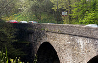 Cars crossing a stone bridge over the River Teith, near the town