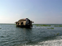 A houseboat moving placidly through a coastal lagoon in Alleppey