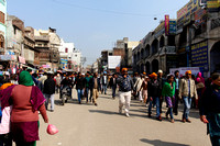 Shops and devotees in a crowded street in front of the Golden Te