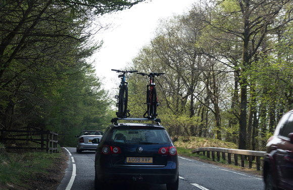 Car on a road in Scotland, with cycles mounted on the top