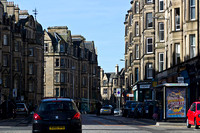 Cars and buildings on a street in Edinburgh with cars parked to