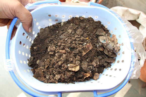 Sieving the compost to remove larger unprocessed items