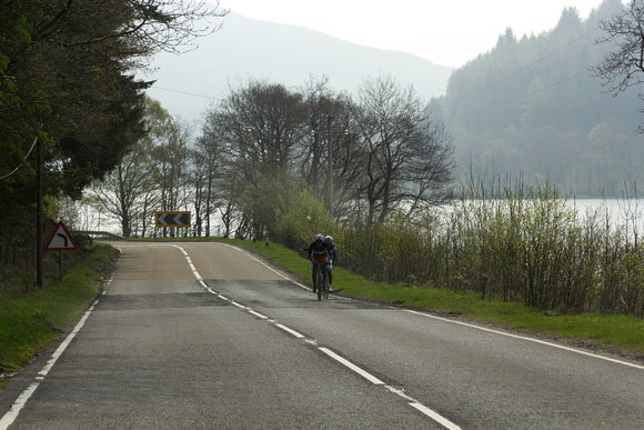 Cyclists on a road in the Scottish Highlands with a lake next to them